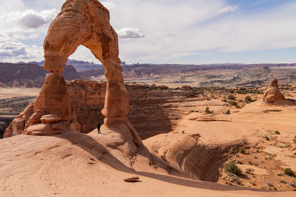 A man stands underneath Delicate Arch with vast desert and rock formations seen in the background at Arches National Park in Moab, Utah.