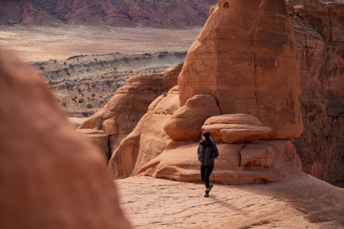 A woman looks out to the desert while standing underneath Delicate Arch in Arches National Park located in Moab, Utah.