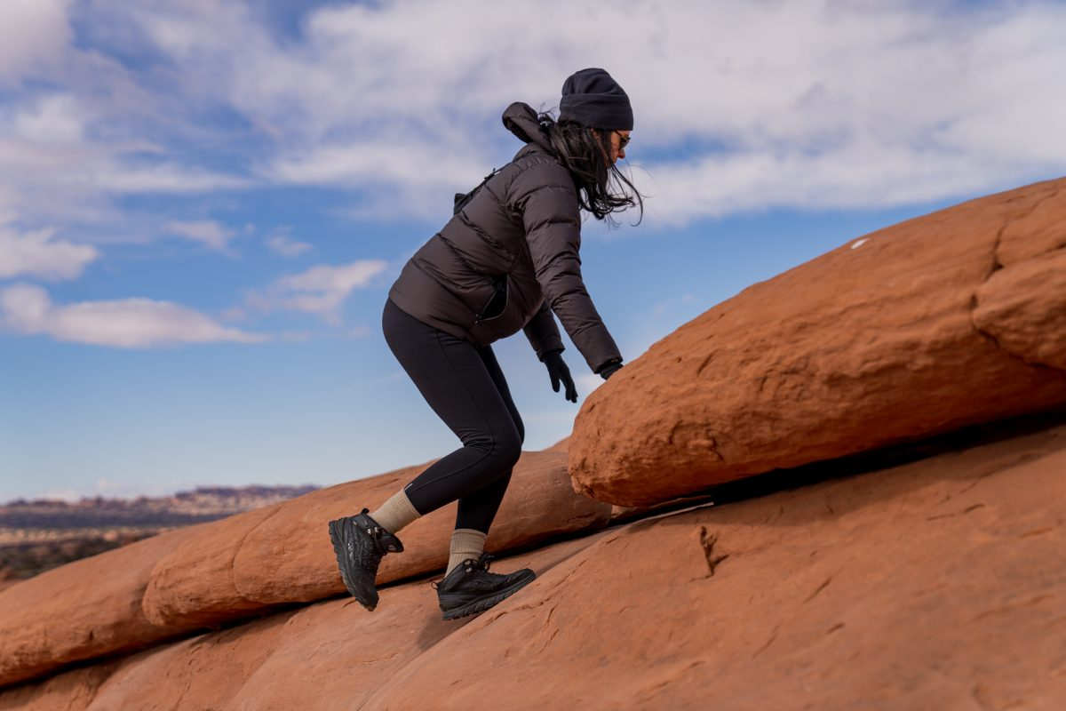 A woman hikes up the slickrock on the Delicate Arch trail in Arches National Park in Moab, Utah.