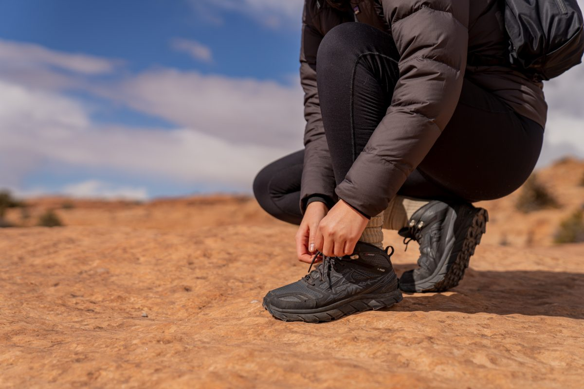 A hiker ties the laces on their hiking boot while on the Delicate Arch trail in Arches National Park in Moab, Utah.