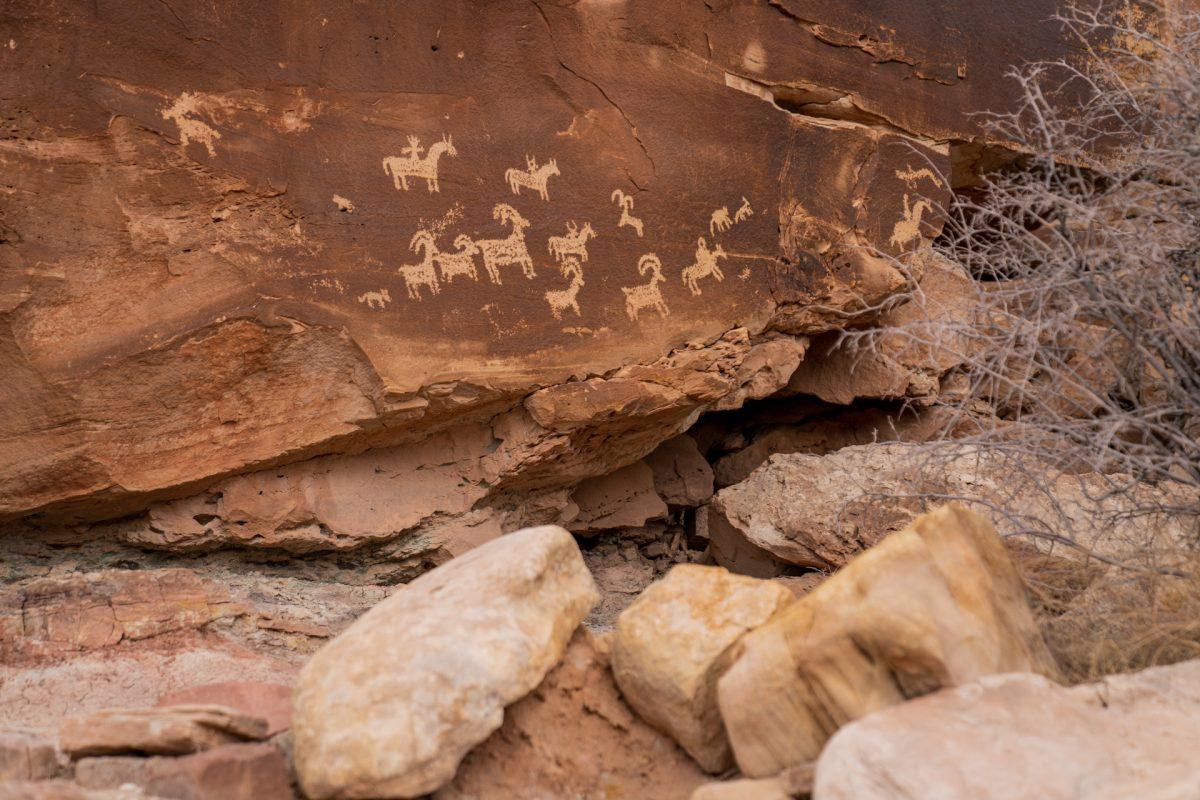 The Ute art petroglyph panel depicting hunters on horses pursuing big horn sheep.