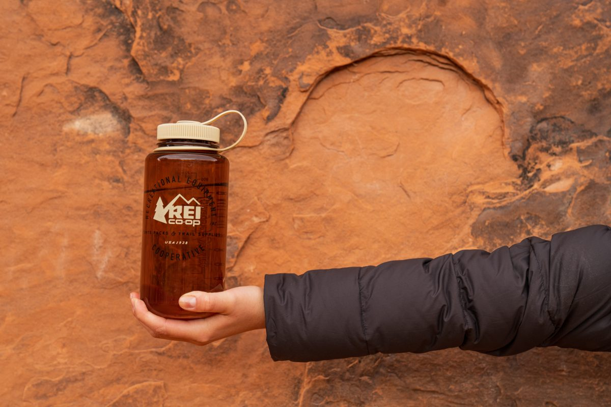 A reusable water bottle is held up in front of red rock at Arches National Park in Utah.