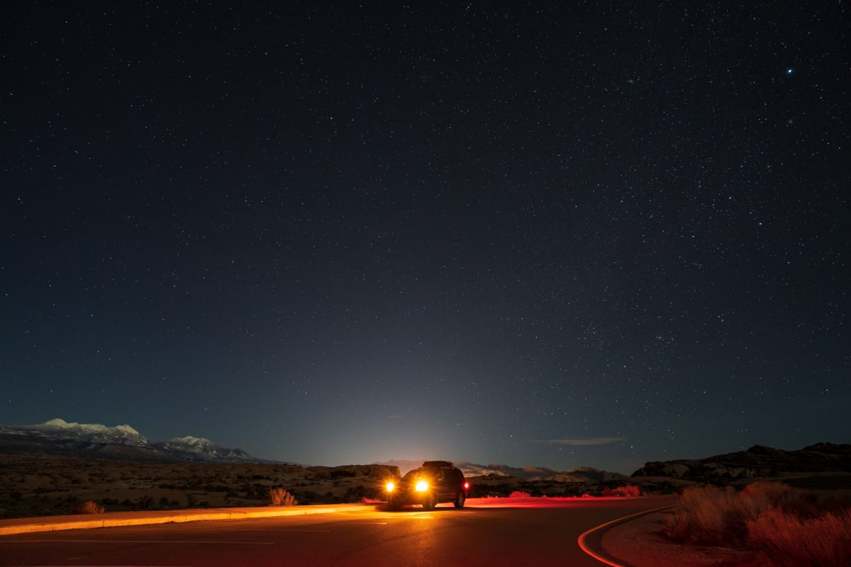 In the night, an SUV shines its lights while parked at the Balanced Rock pull out in Arches National Park in Moab, Utah.