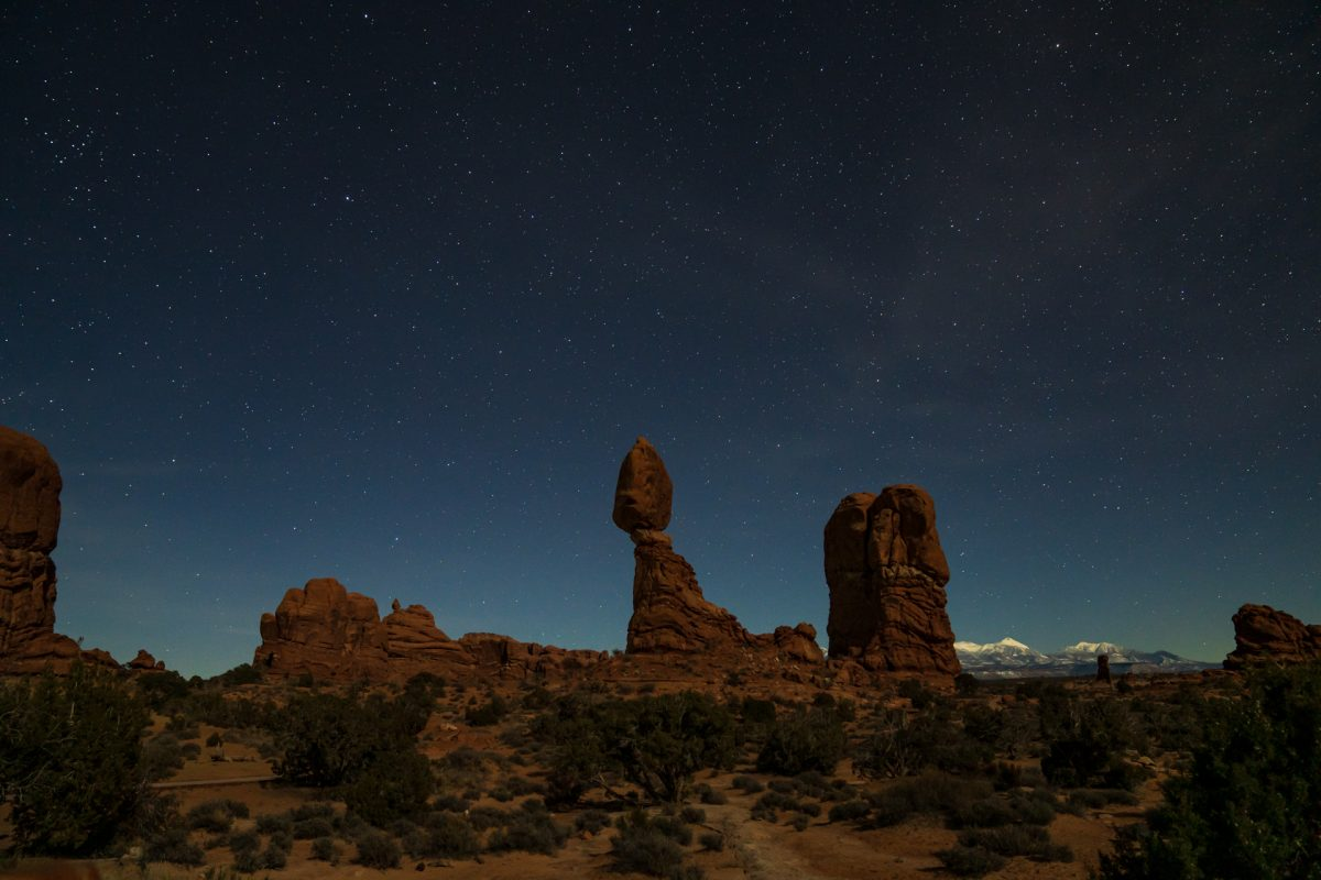 A nighttime image of Balanced Rock in Arches National Park in Moab, Utah. The snow-covered La Sal mountains can be seen in the background.