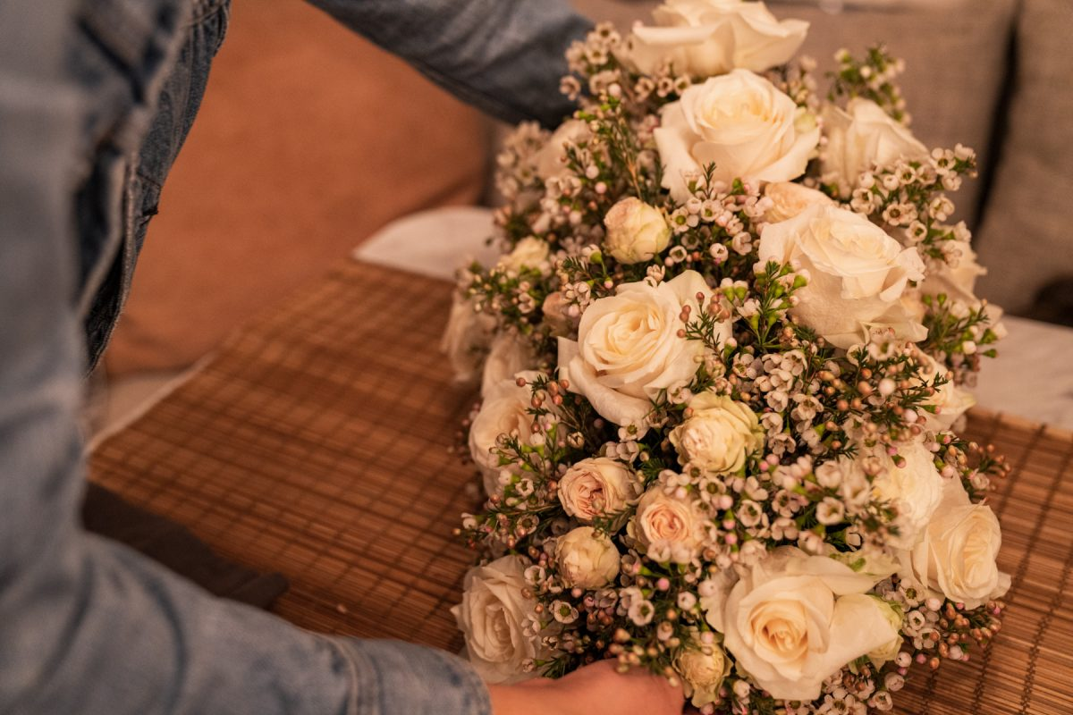 A person sets down a floral arrangement of roses and wax flowers on top of a table within an Airstream RV.