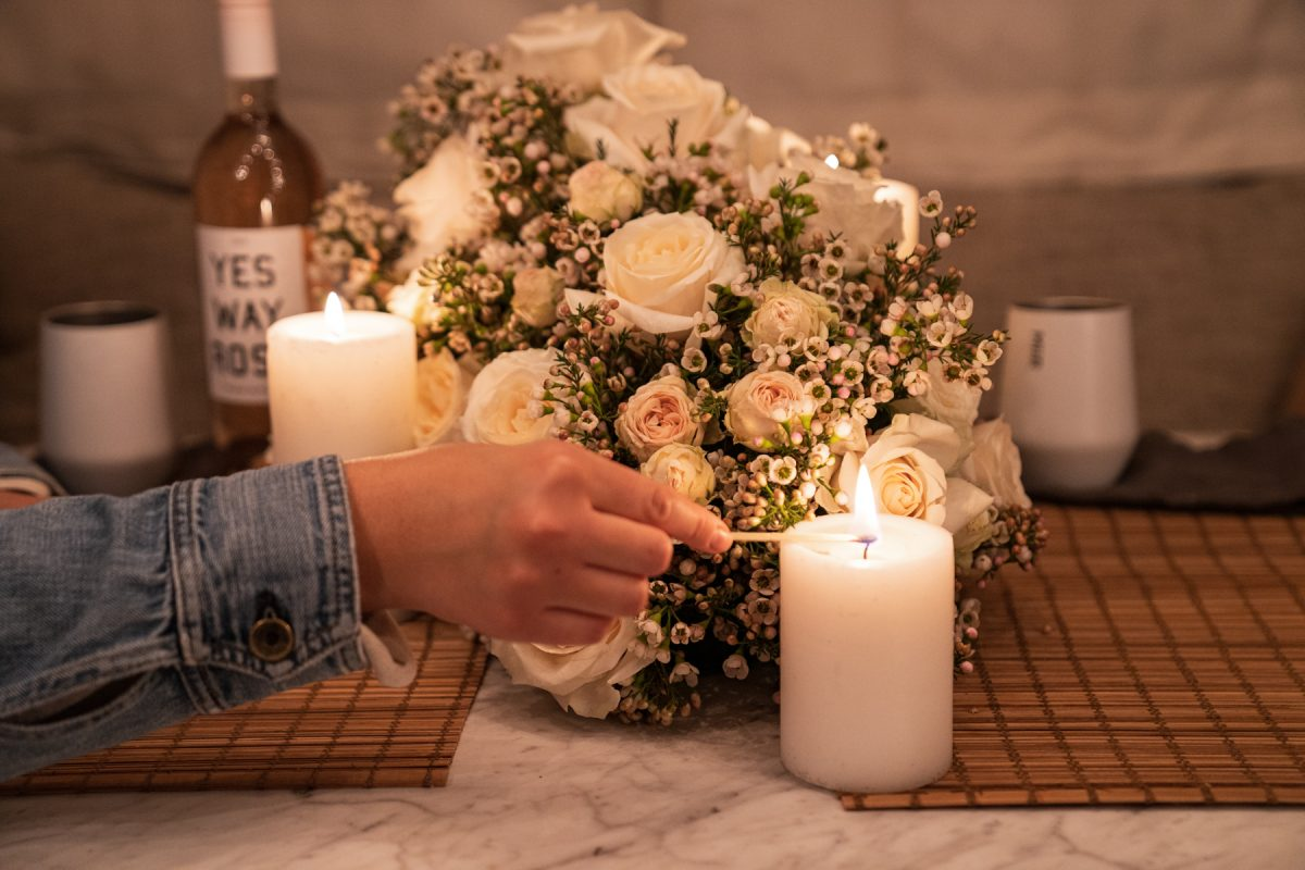A person lights a candle that is sitting on top of an Airstream RV table and next to a floral arrangement of roses and wax flowers.