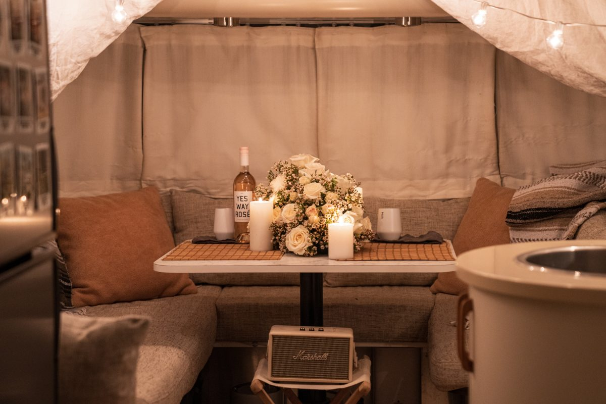 The view of a dinette area of an RV Airstream trailer decorated by Valentine's day flowers, cafe lights, and linen tarps.