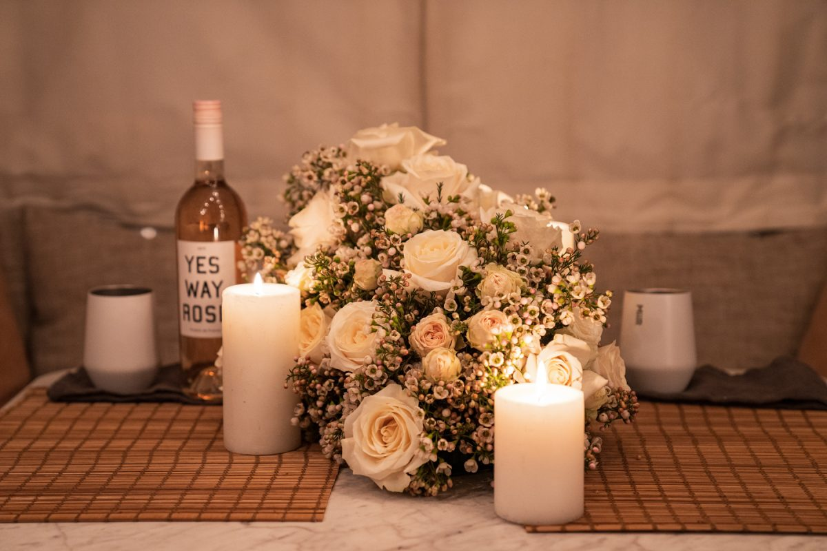 A floral arrangement of roses and wax flowers sits on an RV dinette table surrounded by lit candles, wine, and Miir wine tumblers.