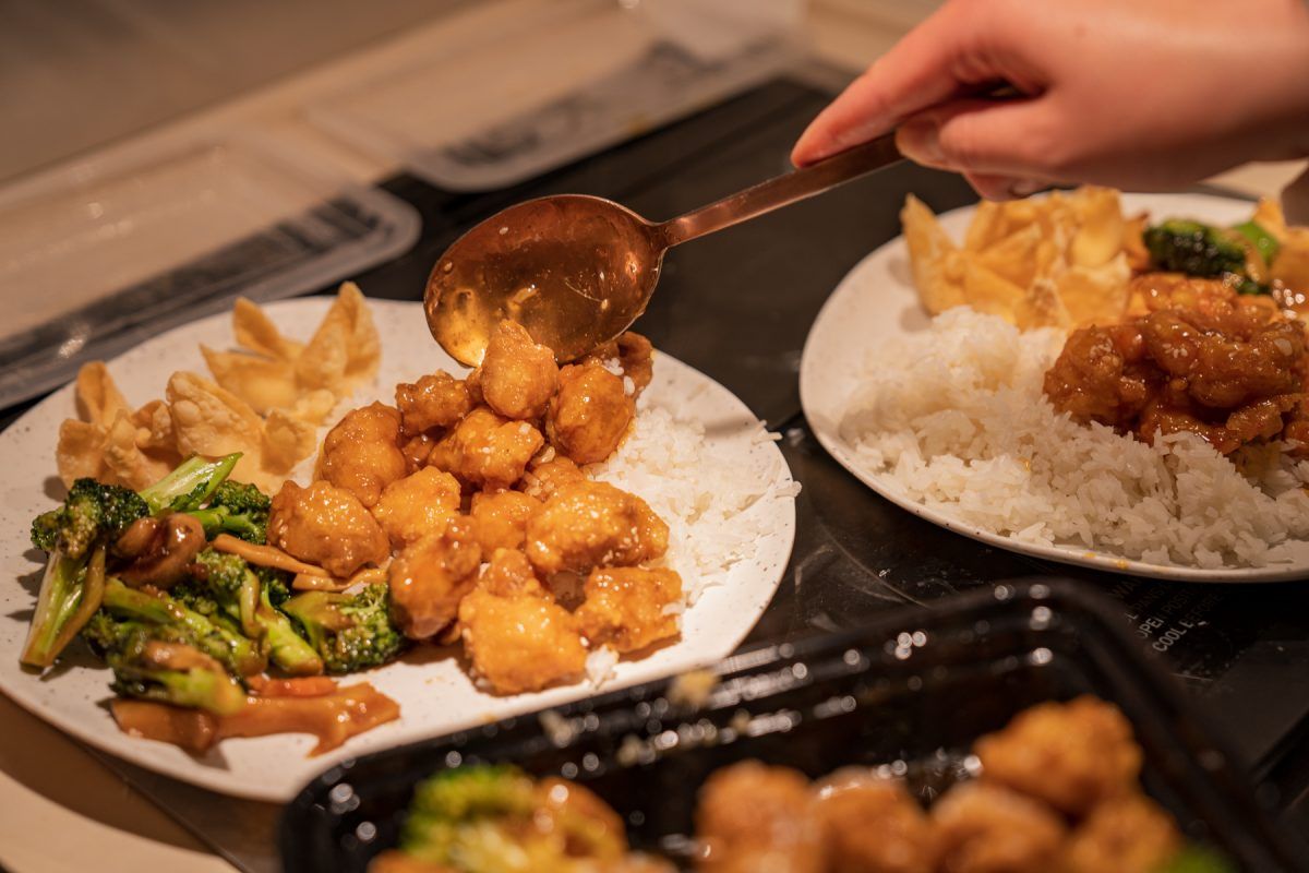 A person serves Chinese takeout onto plates.