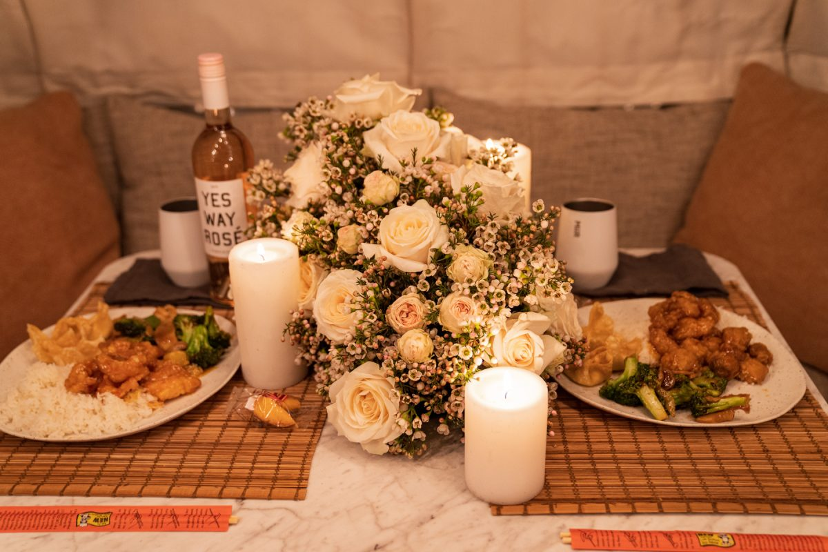 A table spread of Chinese takeout, wine, Miir wine tumblers, lit candles, and a floral arrangement of wax flowers and roses.