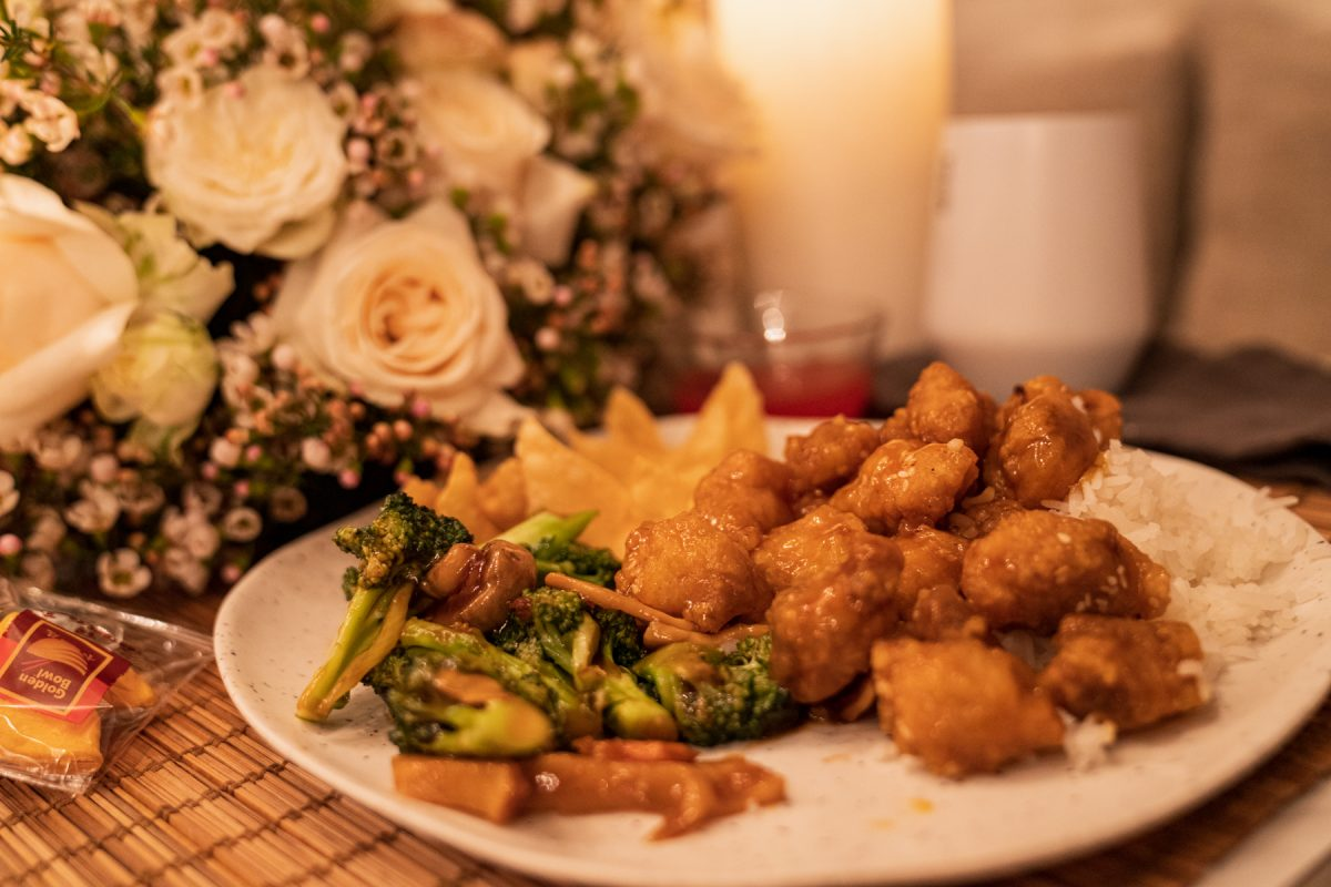 A plate of Chinese takeout, consisting of sesame chicken, vegetable stir fry, and crab rangoon with white rice. In the background is a fortune cookie, a floral arrangement of roses and wax flowers, candles, and a wine tumbler.