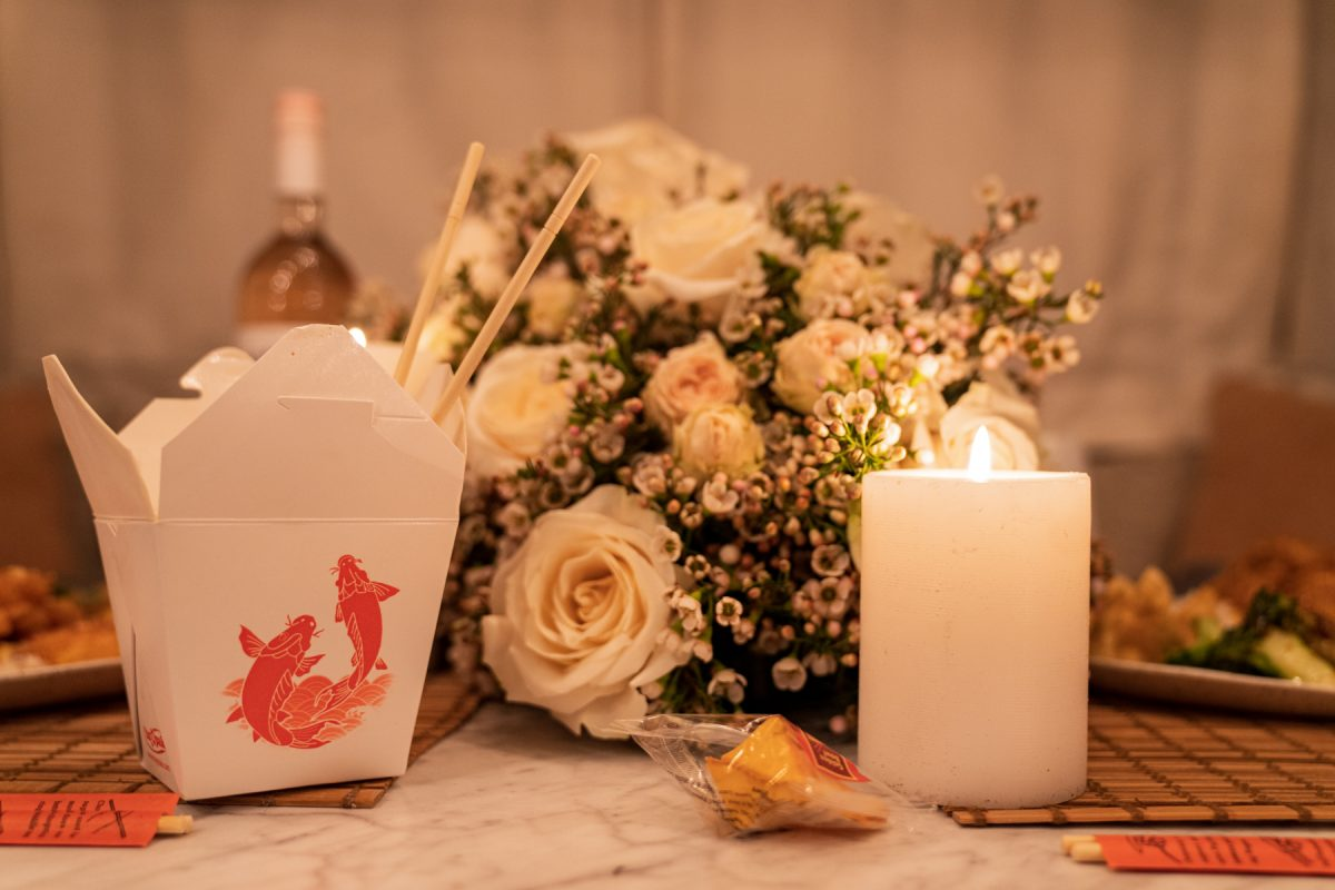 A Chinese takeout box sits next to a lit candle and a floral arrangement of roses and wax flowers. A fortune cookie sits nearby.