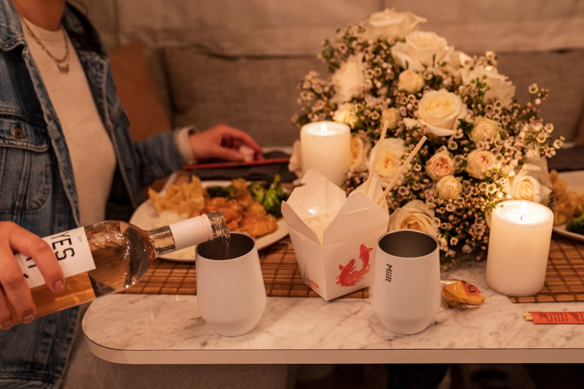 A woman pours rosé wine into a white Miir wine tumbler that is sitting next to her plate of Chinese takeout.