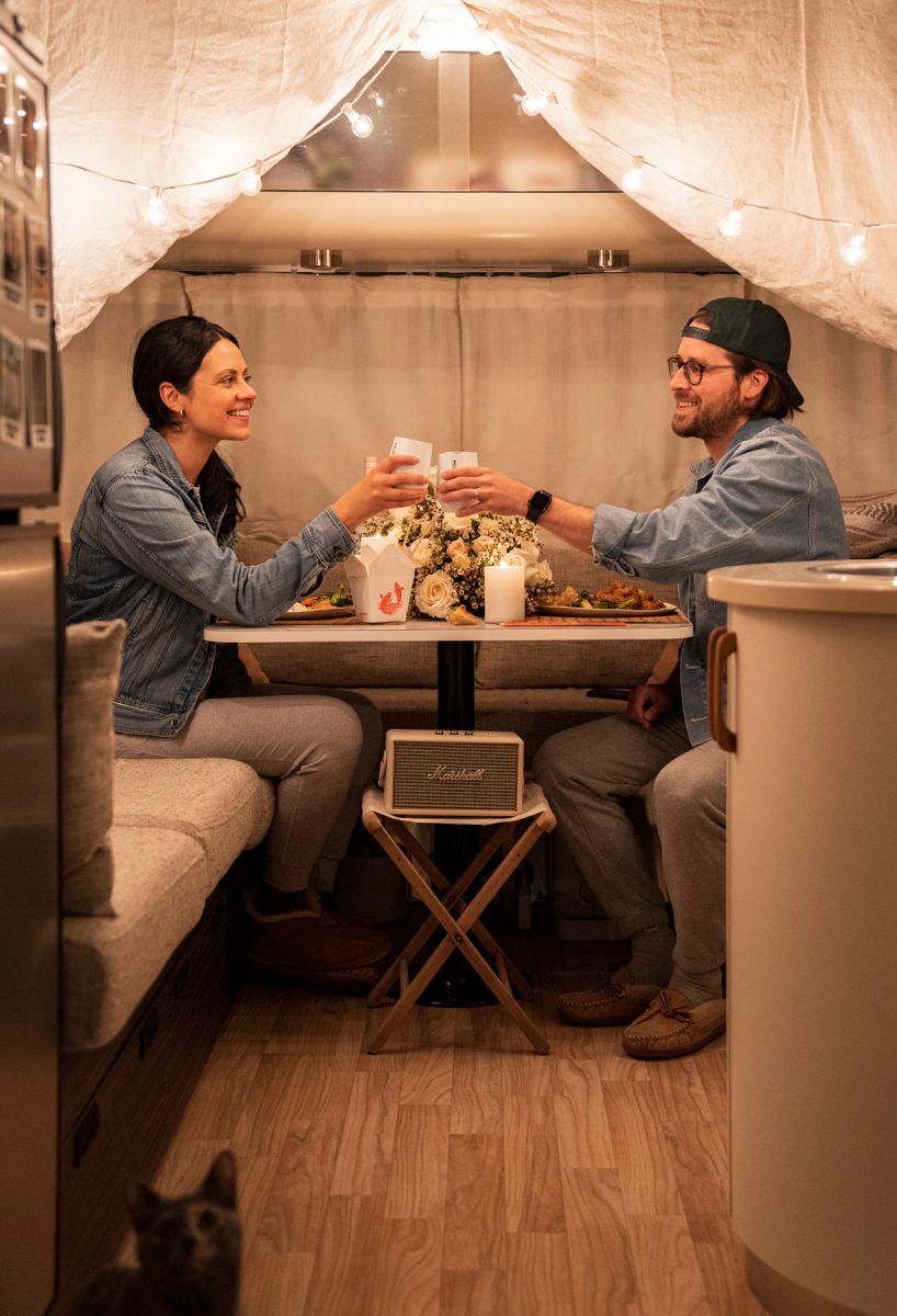 A woman and a man cheers while enjoying a Valentine's date night inside of their Airstream RV trailer.
