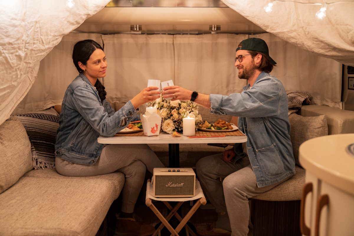 A couple cheers while celebrating Valentine's Day with a date night inside their RV trailer.