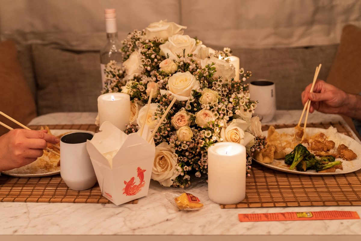 A couple enjoys Chinese takeout while celebrating Valentine's Day by having date night inside their Airstream RV trailer. The pair are using chopsticks. Candles are lit and a floral arrangement of roses and wax flowers sit in the middle of the table.