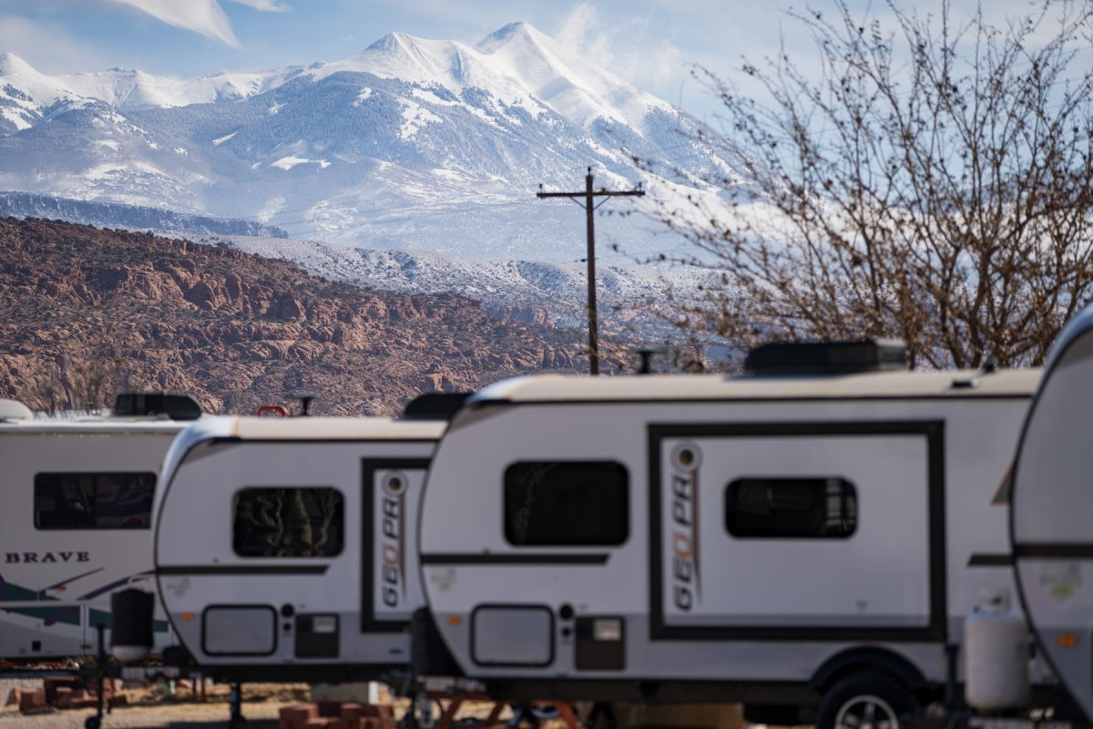 Geo Pro RVs in a line at OK RV Park in Moab, Utah, with snowy La Sal Mountains in the background.