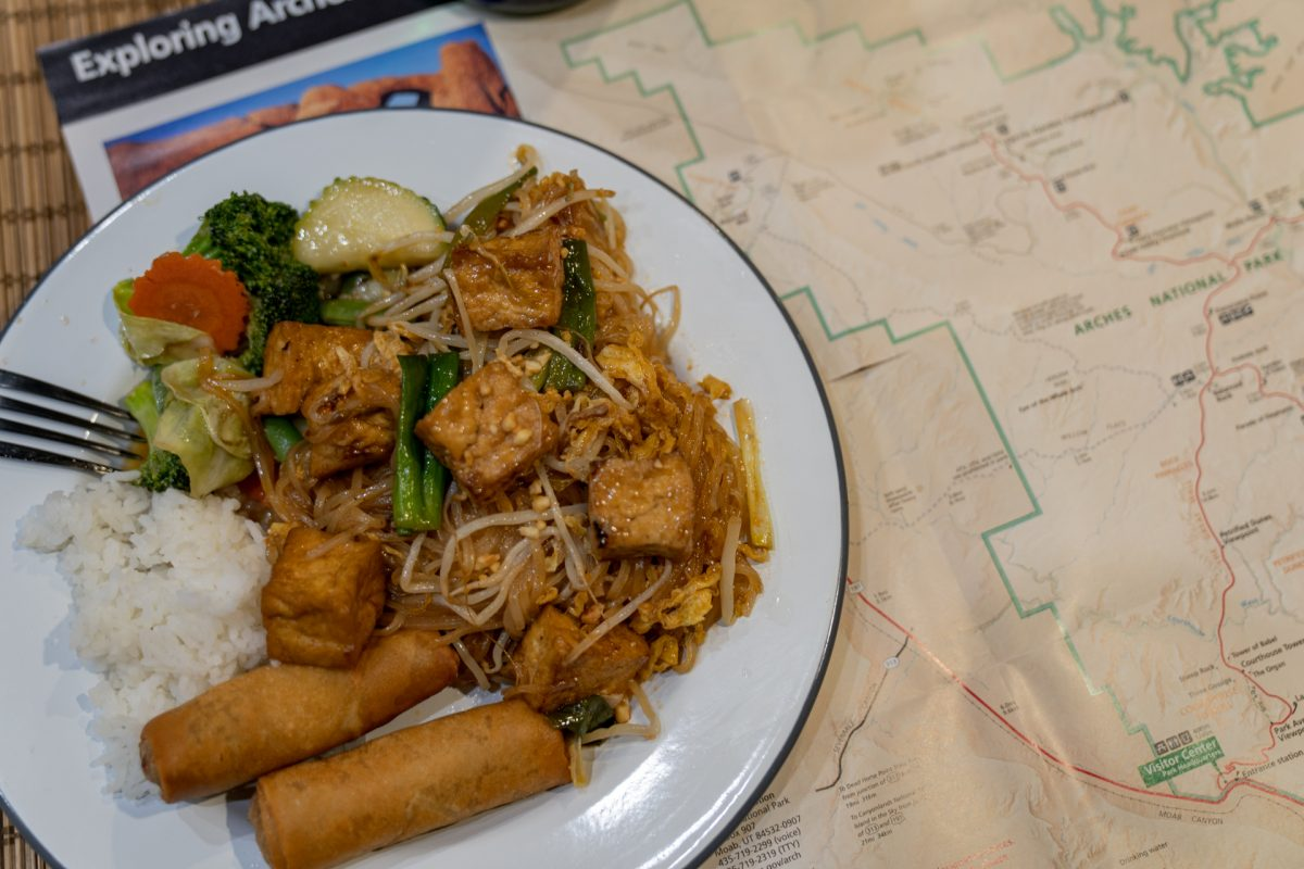 A plate full of rice, vegetables, spring rolls, and Pad Thai sits on top of maps to Arches National Park. The food comes from Thai Bella Moab in Moab, Utah.