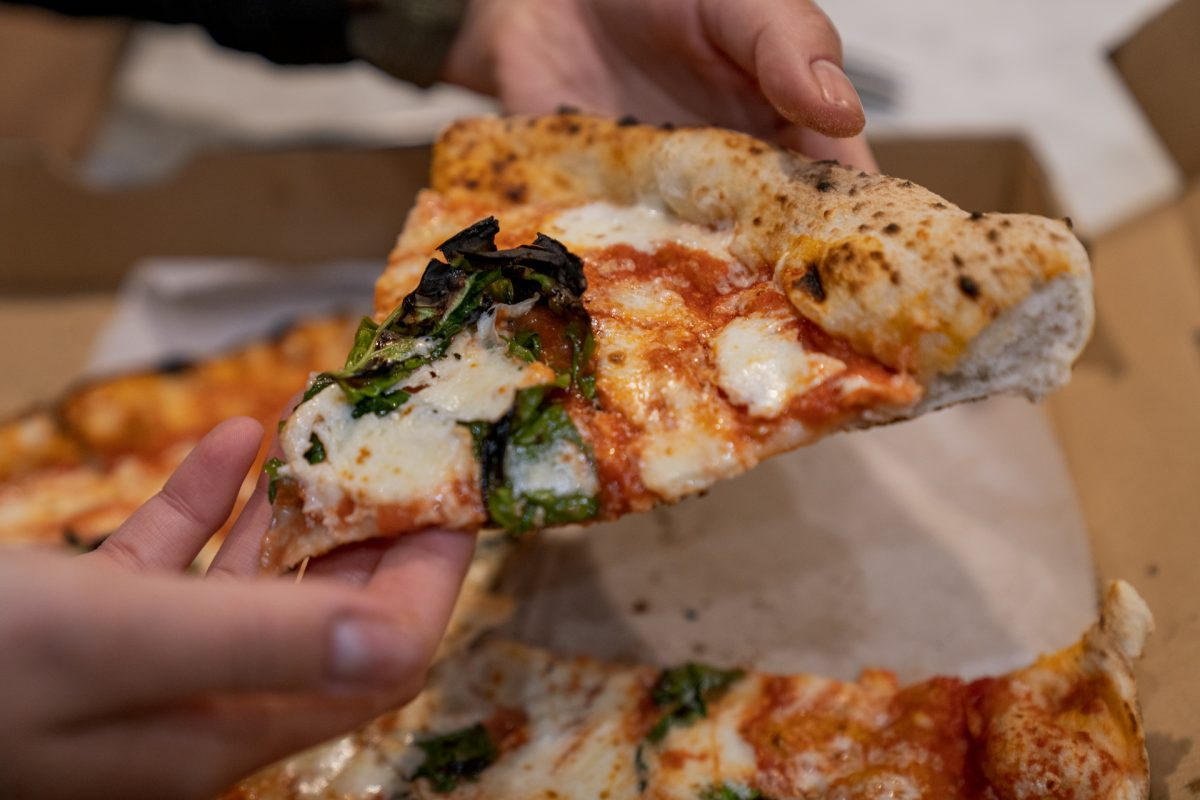 Someone holds a slice of margherita pizza from the restaurant Antica Forma in Moab, Utah.