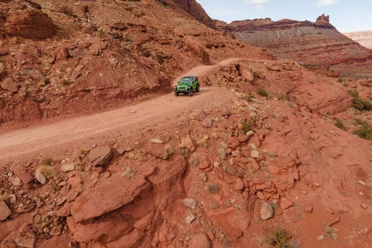 A green jeep rides along the edge of the Gemini Bridges OHV trail in Moab, Utah.