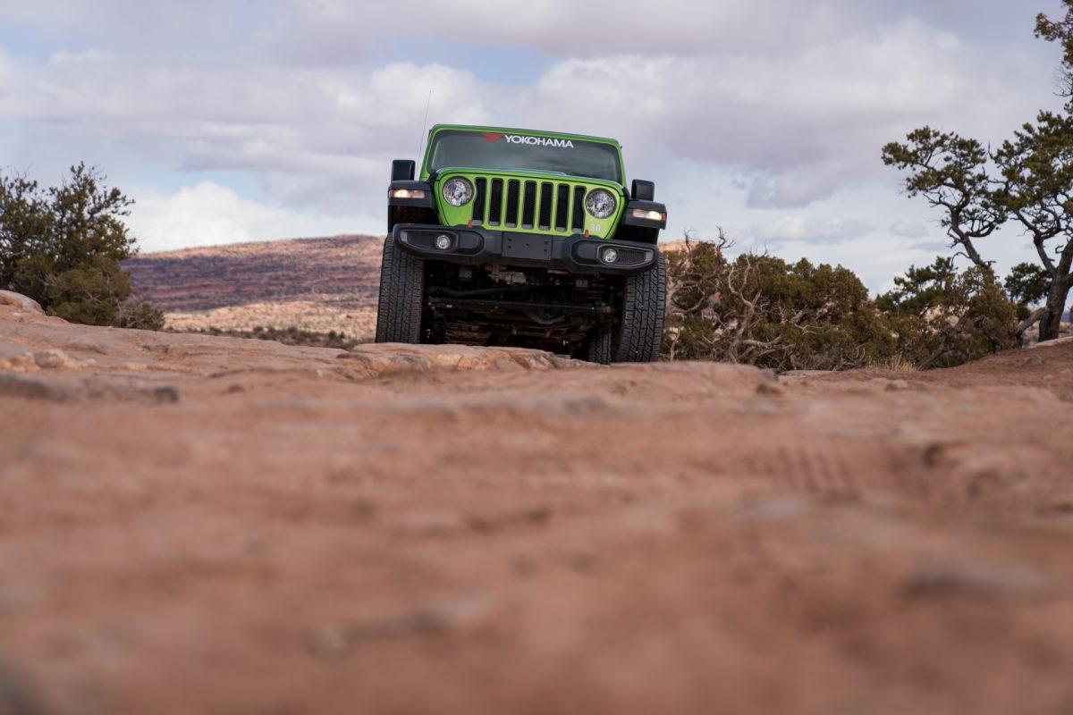 A green jeep climbs over sandstone slickrock on the Gemini Bridges OHV trail in Moab, Utah.