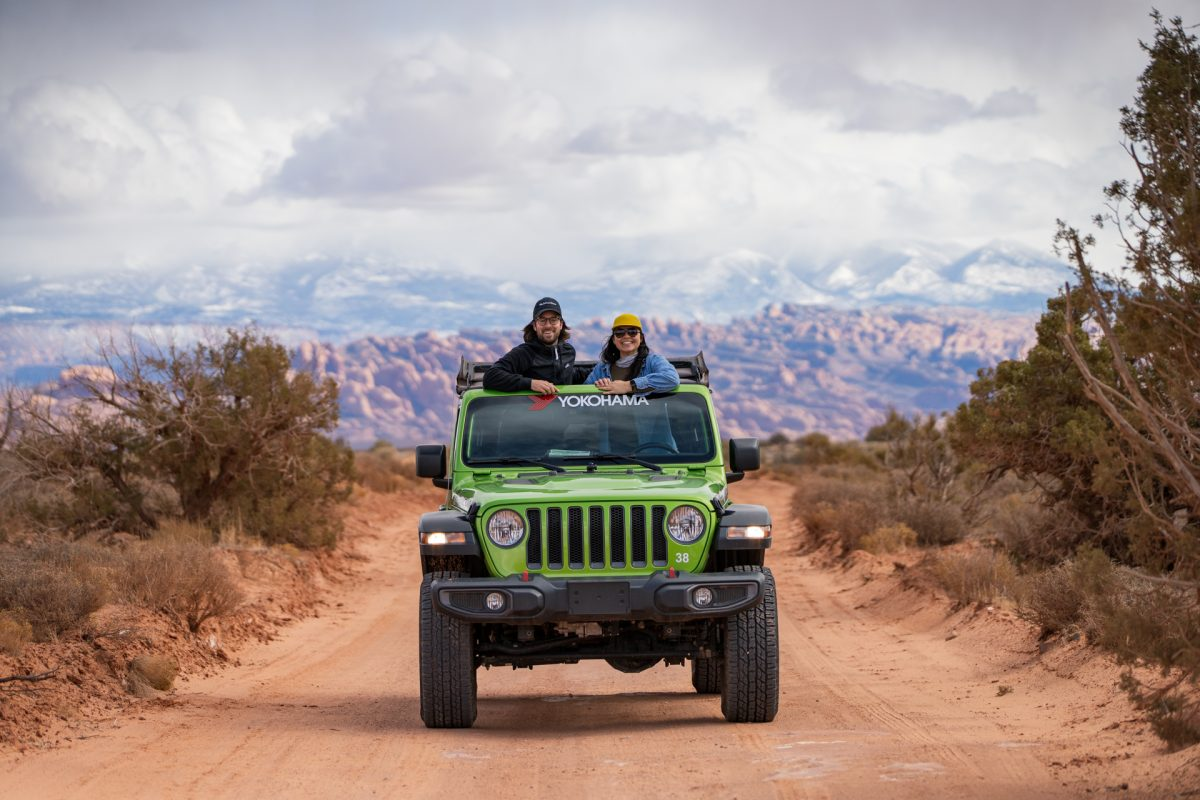 A couple peeks their heads out of the sunroof of a green jeep on the Gemini Bridges OHV trail in Moab Utah. The La Sal Mountains are in the back.