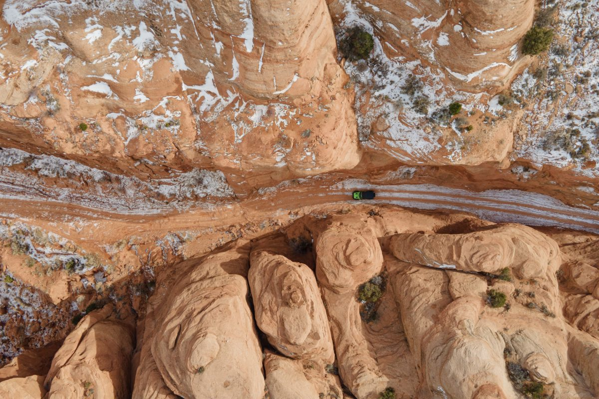 A green jeep goes through a row of sandstone spires on the Long Canyon OHV trail in Moab, Utah.