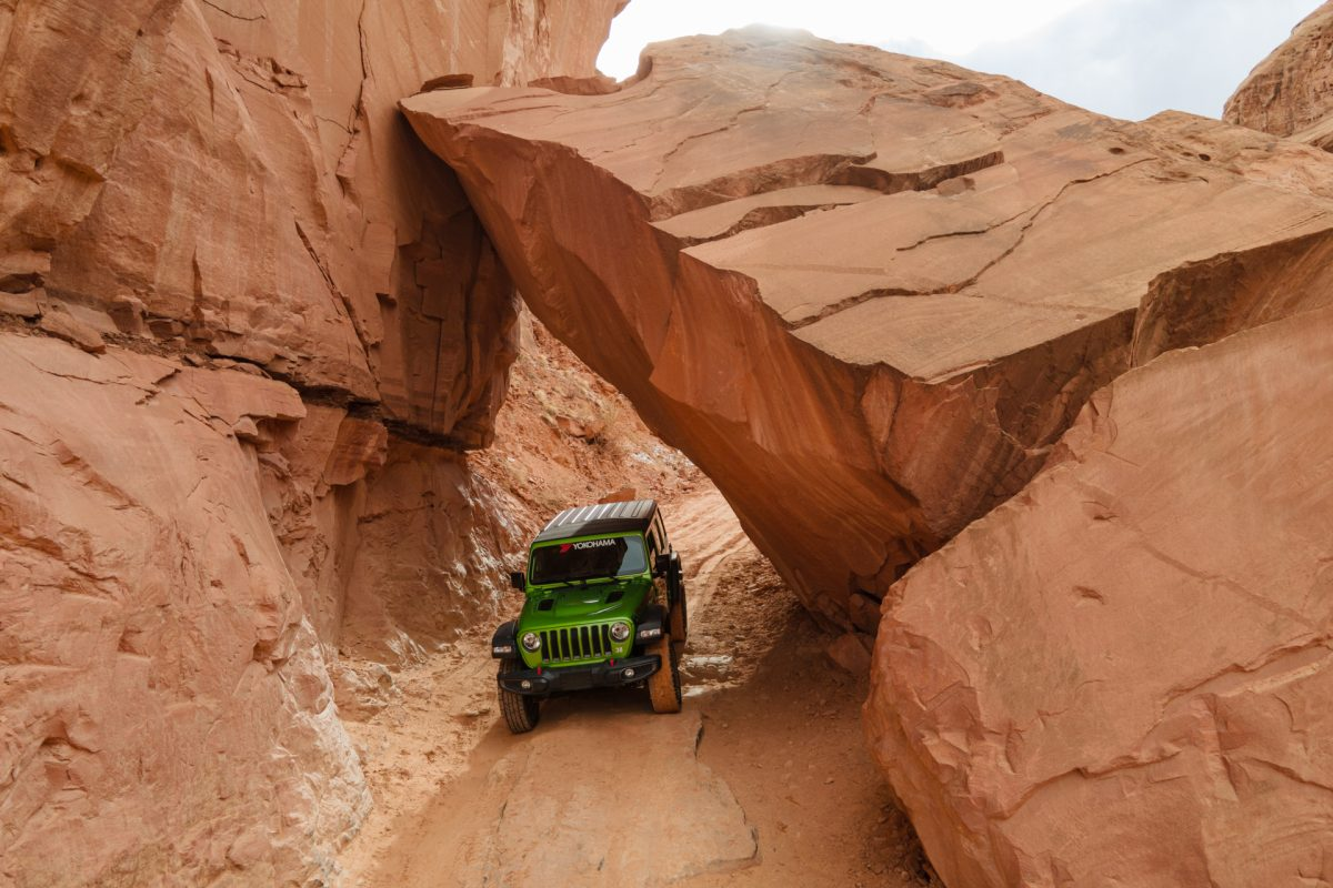 A green jeep goes under a giant boulder on the Long Canyon OHV trail in Moab, Utah.