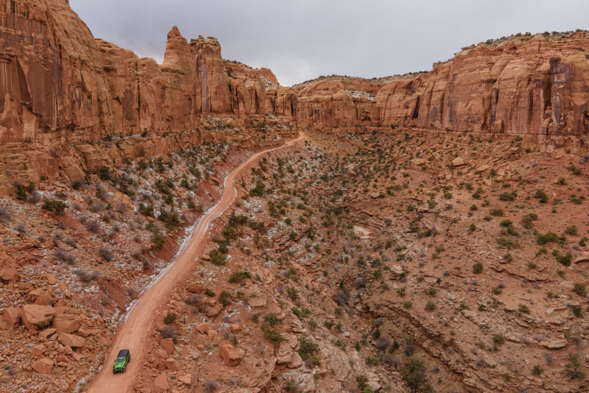 An aerial view of a green jeep driving down Long Canyon OHV trail in Moab, Utah.