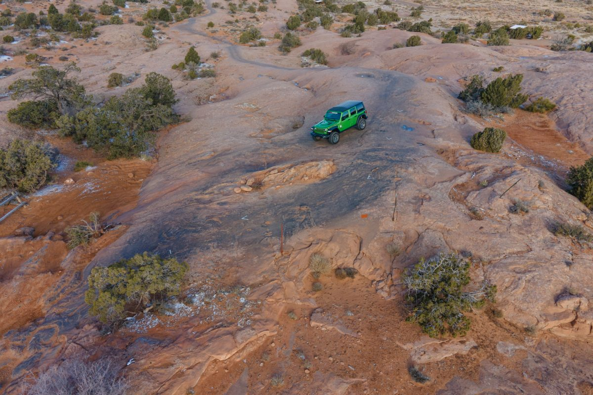 A green jeep on slickrock on the Fins & Things OHV trail in Moab, Utah.