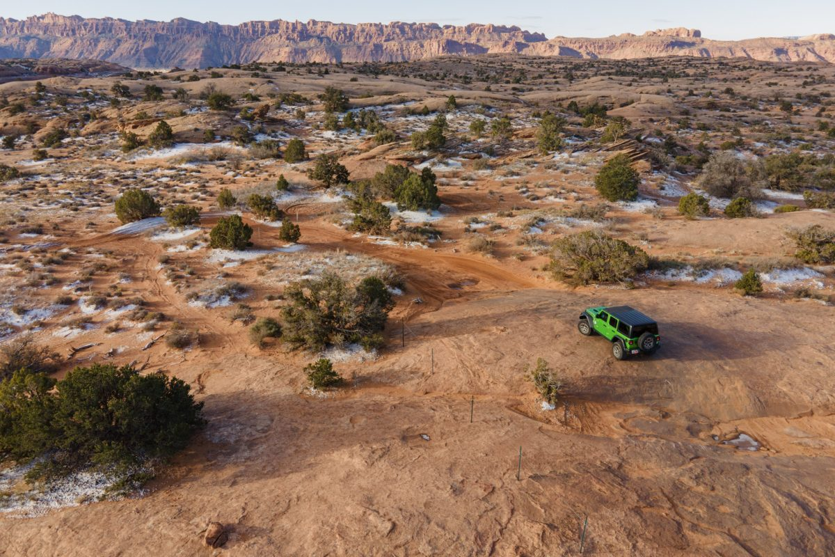 A green jeep on slickrock in Fins & Things OHV trail in Moab, Utah.