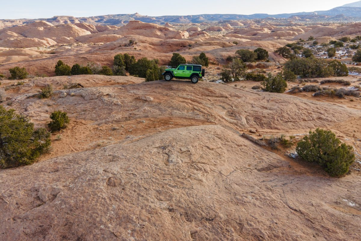 A green jeep sits on top of a sandstone fin on Find & Things trail in Moab, Utah.
