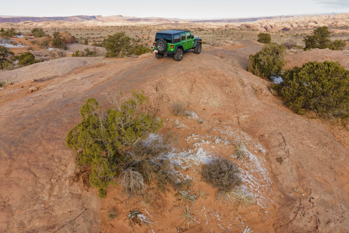 A green jeep sits on top of a sandstone fin on the Fins & Things OHV trail in Moab, Utah.