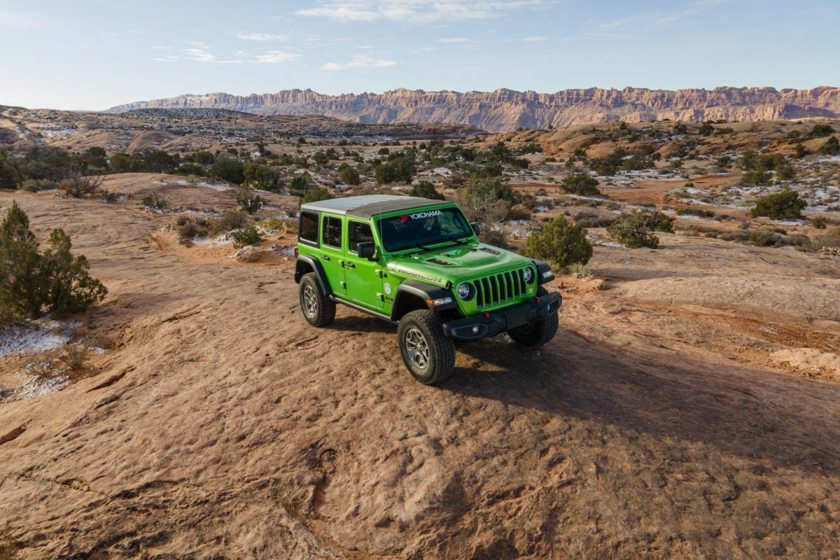A green jeep sits on top of slickrock on Fins & Things OHV trail in Moab, Utah.
