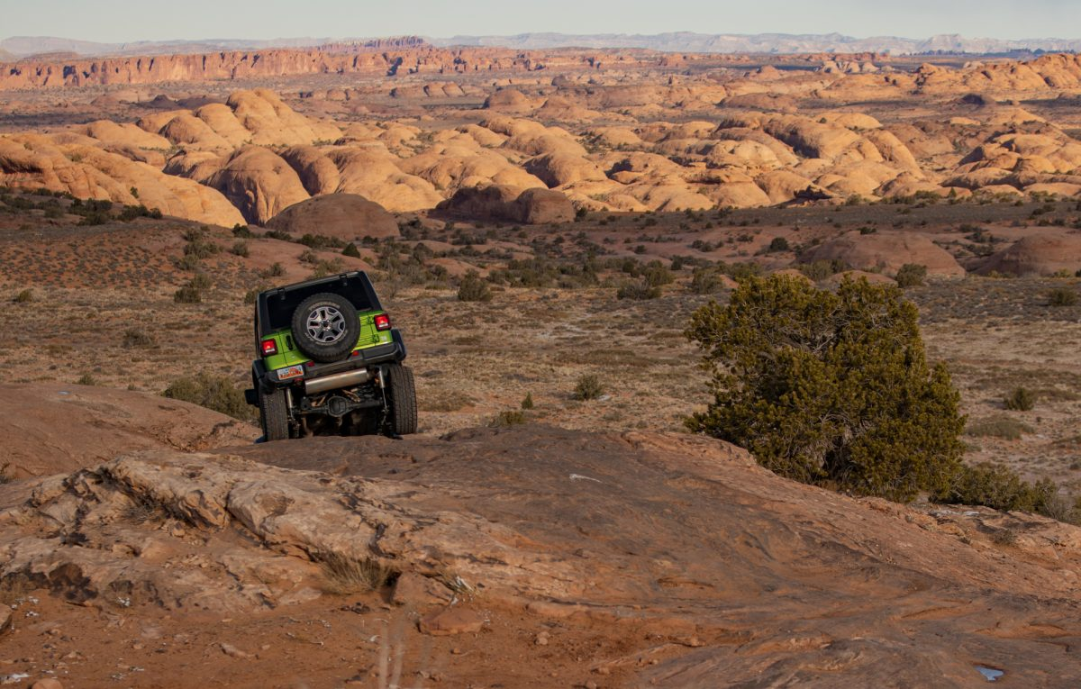 A green jeep goes down a slickrock fin on the Fins & Things OHV trail in Moab, Utah.