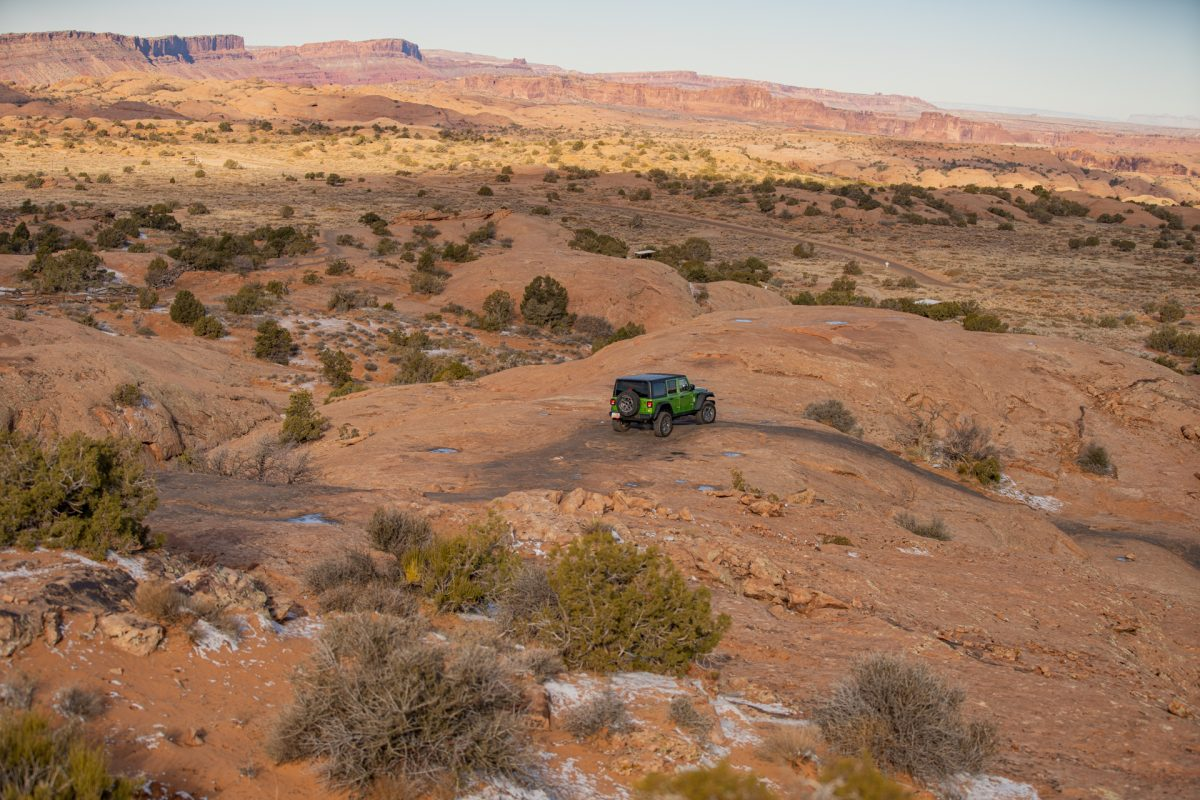 A green jeep drives on top of slickrock at the Fins & Things OHV trail in Moab, Utah.