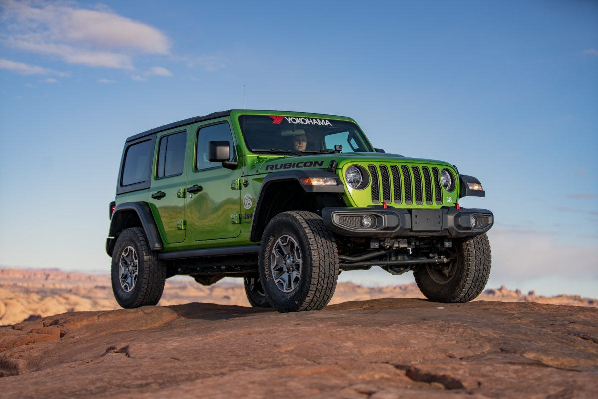 A green jeep sits on top of slickrock on the Fins & Things OHV trail in Moab, utah.