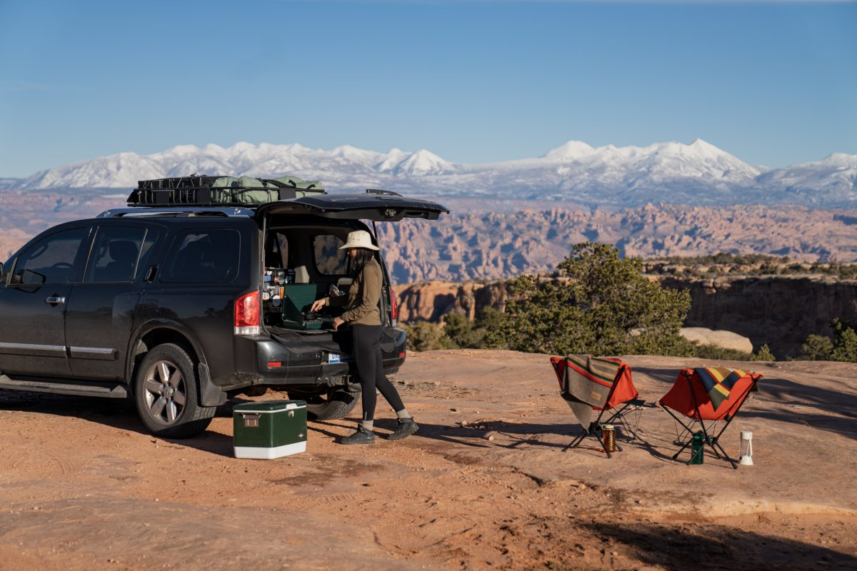 A woman makes grilled cheese on a camp stove in the back of a black SUV. In the background, the La Sal Mountains near Moab, Utah, can be seen.