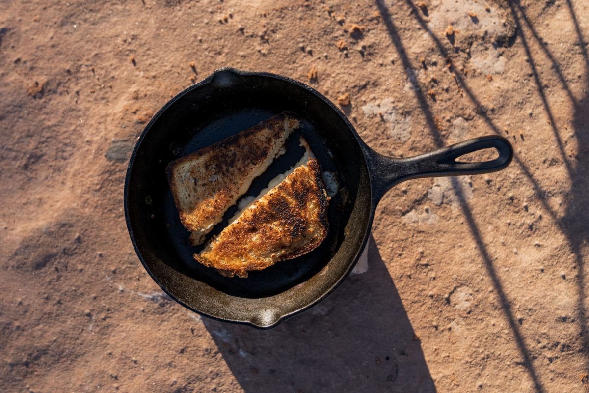 A grilled cheese cut in half, sitting in a cast-iron pan.