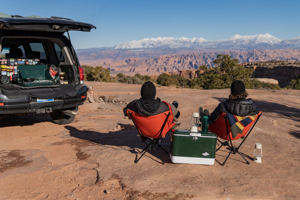 Two people sit in REI camp chairs while looking out to the La Sal Mountains near Moab, Utah.
