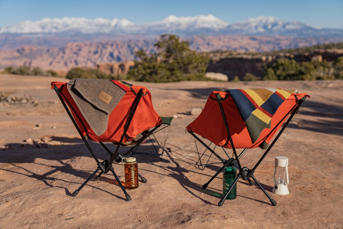 Orange REI camp chairs with Pendleton blankets sitting on top of them, facing toward the La Sal Mountains near Moab, Utah.