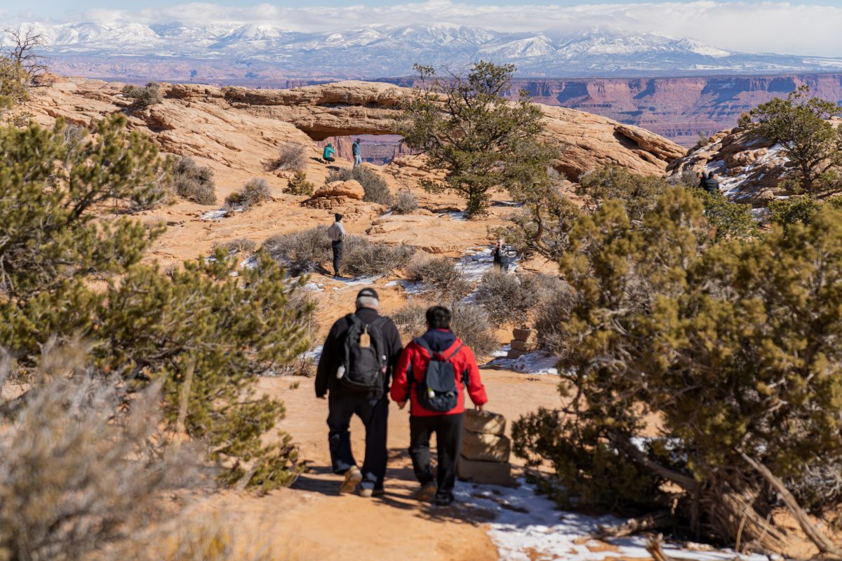 A couple hikes the Mesa Arch trail with the La Sal Mountains and Mesa Arch in the background at Canyonlands National Park near Moab, Utah.