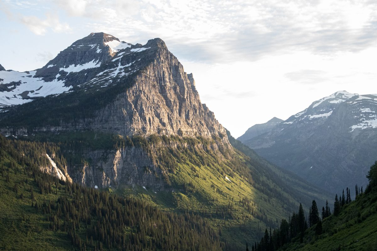 The sun rises on a mountain and valley at Glacier National Park in Montana.
