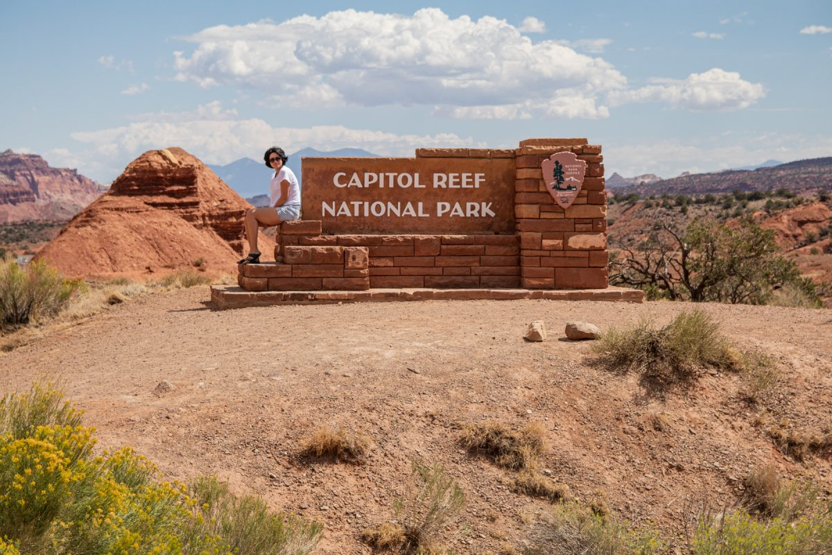A woman sits on the Capitol Reef National Park sign in Utah.