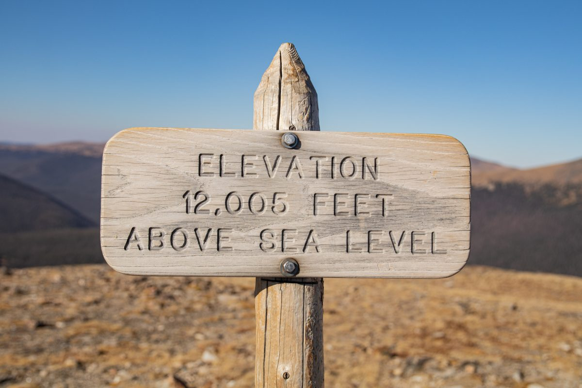 """A sign that reads """"Elevation 12,005 feet above sea level"""" at Rocky Mountain National Park in Colorado."""
