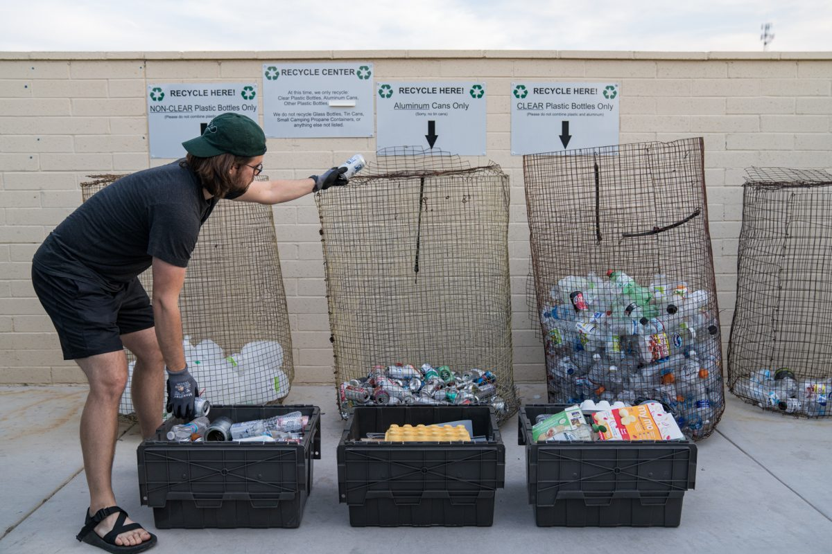 A man separates his recyclables into different recycling bins at a Sonoran RV Resort in Gila Bend, Arizona.