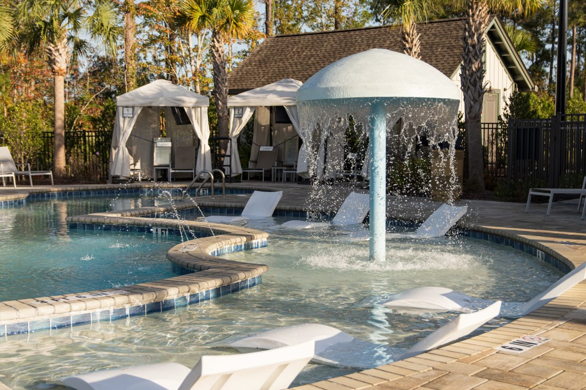 Pool with cabana surrounded by palm trees at Carolina Pines RV Resort