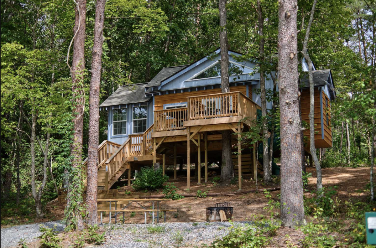 Family treehouse nestled in the woods with a fire pit and picnic table