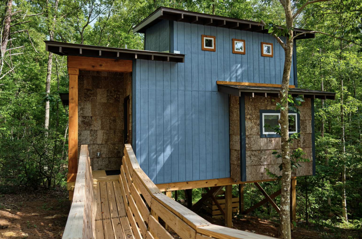 Blue tree house in the woods with walkway