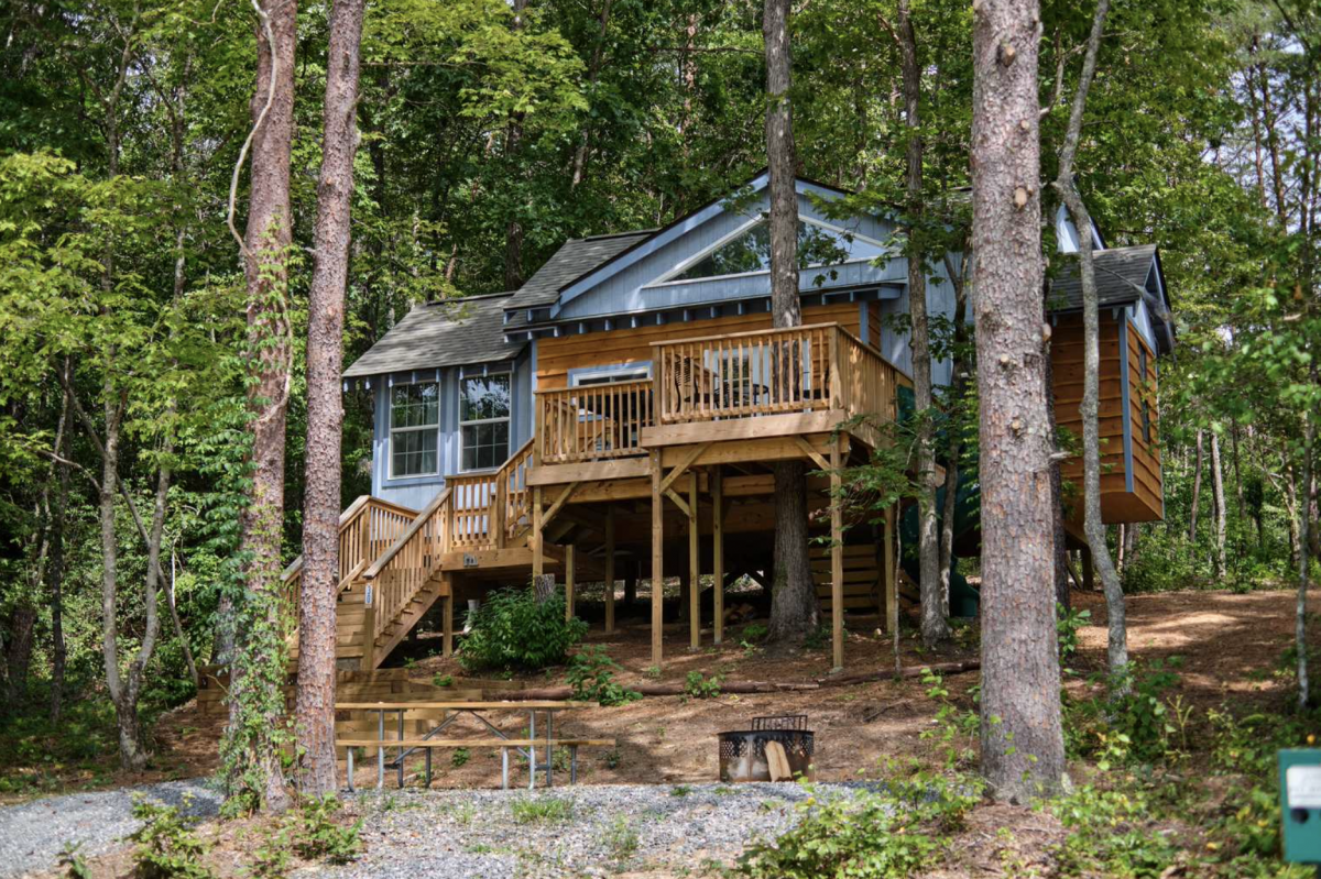 Blue family treehouse in the woods with a picnic table and outdoor fire ring.